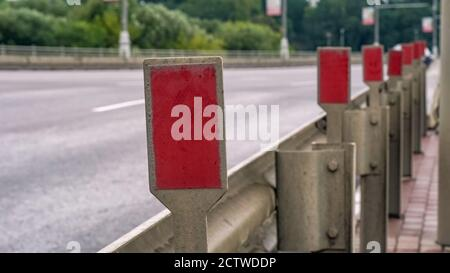 Barrier warning fence from the road with cars on the bridge - Stock Photo