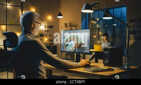 In the Evening Creative Middle Aged Video Game Developer Works on a Desktop Computer with Screen 3D Videogame Level Design. Professional Office