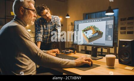 In the Evening Creative Middle Aged Video Game Developer Works on a Desktop Computer with Screen 3D Videogame Level Design, Has Conversation with