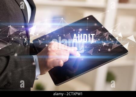 Close up hands using tablet with AUDIT inscription, modern business technology concept