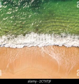 An aerial drone image looking down onto a sandy beach with white rolling waves and surf crashing onto a beach from an emerald green ocean in Cornwall, - Stock Photo