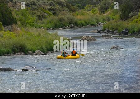 New Mexico -USA   September 16 2015; Group of people paddling inflatable along Rio Grande river through landscape of New Mexico, USA.