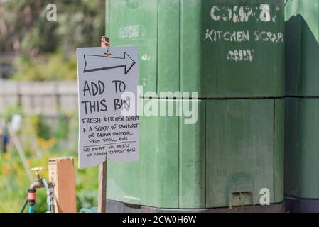 A sign in a community garden in the Sydney, Australia, suburb of Annandale pointing to a large green compost bin for vegetable scraps - Stock Photo