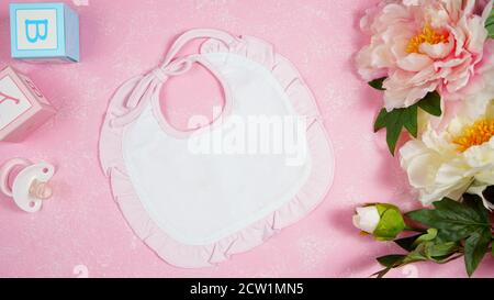 Baby bib nursery clothing mom bloggers desktop mockups with peonie floers on pink textured background. Top view blog hero header creative composition