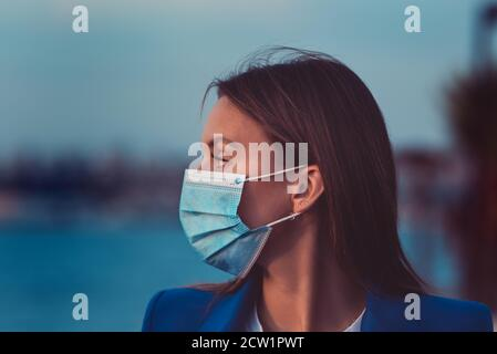 Beautiful woman in a disposable medical mask. Protection against coronavirus Stock Photo