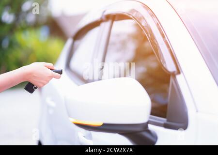 Closeup woman hand holding the remote control car alarm systems