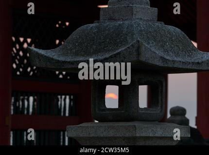 The view of burning gold sunset light through the fire box (hibukuro) of the stone lantern representing the fire (Ka) from the five elements of Buddhi