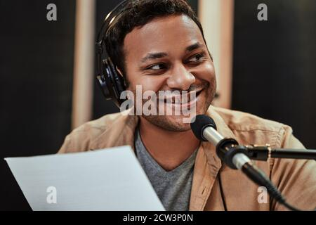 Close up portrait of happy young male radio host in headphones smiling aside while talking, broadcasting in studio