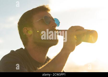A young man, with glasses and a beard, drinks beer from a bottle, while enjoying the landscape and the sunset, in Galicia, northern Spain.