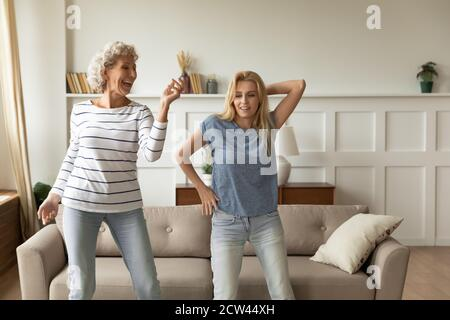 Younger and elder women of different generations dancing having fun - Stock Photo