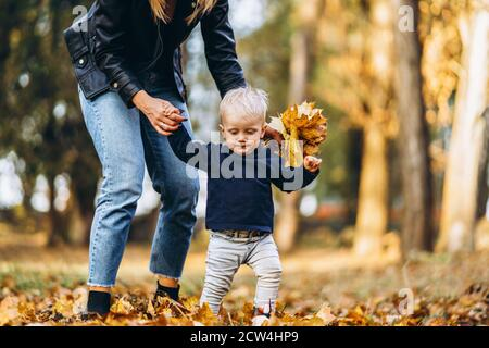 Happy mother with her little baby son have fun in the city park with colorful leaves around in autumn time. Happy family, mother's day concept