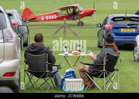 Old Warden Aerodrome, Biggleswade, Bedfordshire, UK. 27th Sep, 2020. In order to comply with the COVID-19 guidelines the Shuttleworth Collection have proceeded with their season of airshows by making them drive-in events. To avoid visitors gathering at the fence line during the flying displays they must stay within a box around their cars which are parked on the grounds facing the runway. Many have laid out picnics beside their cars. The show highlighted the centenary of de Havilland Aircraft with a large number of historic planes taking part. People with camping table and chairs