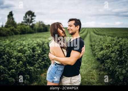 A tender loving couple walking in a field of currant. Man whirls woman in her arms. Love story. - Stock Photo