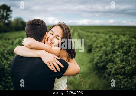 Cute young girl with long hair hugs her lover, smiling and with her eyes closed. Young couple walking in a field in nature.