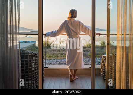 Beautiful woman from back in bathrobe on terrace of hotel room with Sea View - Stock Photo