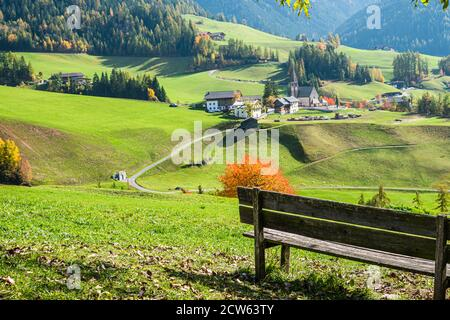 The bench with scenic view at the village of Santa Magdalena in northern Italy on the slopes of the Dolomites in the valley of Val di Funes.