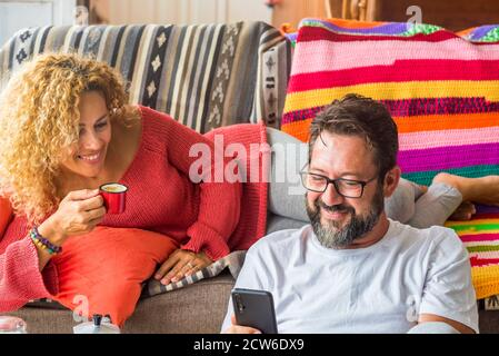 Cheerful adult couple enjoy time together at home having breakfast in the morning - wake up in real life with happy caucasian people - concept of shar