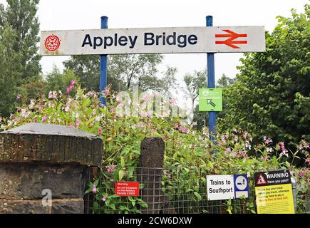 The station sign's at Appley Bridge on a wet morning in Greater Manchester.  The signs still include the old British Railways Double Arrow symbol. Stock Photo