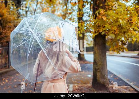 Fashionable woman in autumn clothes walks outdoors under transparent umbrella during rain. Fall season weather.
