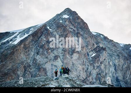 Zinal, Switzerland - July 19, 2019: Back view of hikers team with backpacks walking on rocky path and heading to mountaintop. Concept of travelling, hiking and mountaineering.