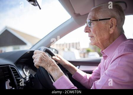 Worried Senior Male Driver Looking Through Car Windscreen - Stock Photo