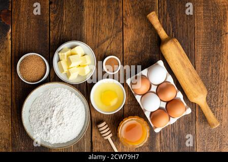 Ingredients for baking on wooden table background. Flour eggs butter sugar spices and honey, cooking gingerbread cookies. Christmas baking