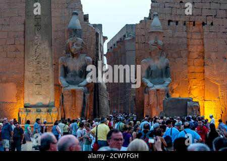 A crowd of tourists gather at the entrance pylon of the Luxor Temple (Temple of Amun-Ra) at Luxor in Egypt at sunset. - Stock Photo