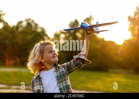 Little boy playing with toy plane in park