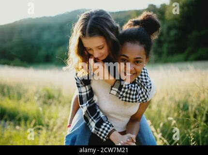 Front view of young teenager girls friends outdoors in nature, having fun.