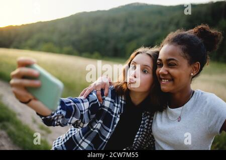 Front view of young teenager girls friends outdoors in nature, taking selfie. - Stock Photo