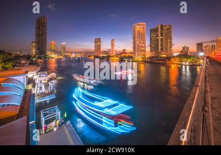 Skyscrapers and Light Trails of Traffic on the Chao Phraya River in Bangkok, Thailand as Seen from Taksin Bridge at Might