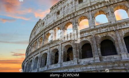 The Colosseum in Rome, Italy in the early evening with a colorful sky in the background.