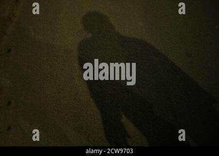 Blurry shadow and silhouette of a man standing in the nights