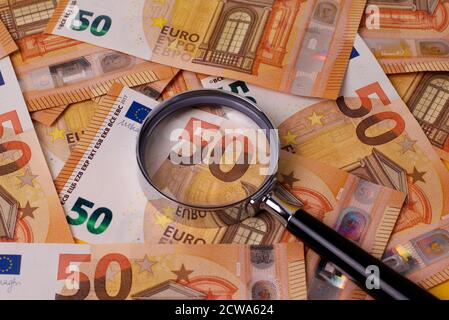 A lot of 50 euro banknotes spread out on a table, with a magnifying glass.