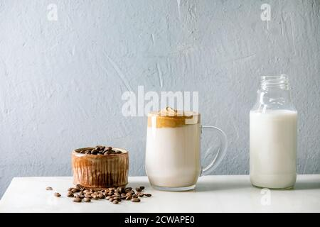 Dalgona frothy coffee trend korean drink milk latte with coffee foam in glass mug with ingredients in row on white marble table. - Stock Photo