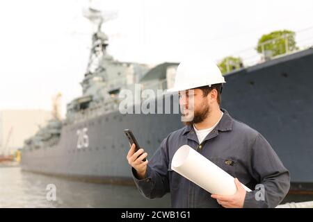 Marine engineer talking by VHF walkie talkie, holding papers near vessel in background.