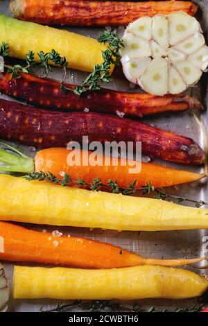 Close up of Ready for baking peeled colorful raw carrots with oil, fresh thyme herbs and sliced garlic in aluminum tray. Top view.