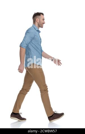 Side view of happy casual man laughing and wearing blue shirt, stepping on white studio background - Stock Photo