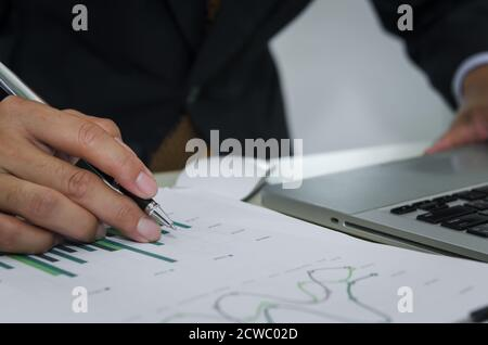 Business man holding a pen, business documents, reports, graphs and charts of financial statements and profit growth Stock Photo