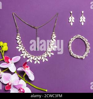 Elegant gold necklace bracelet and earrings with diamonds on purple background