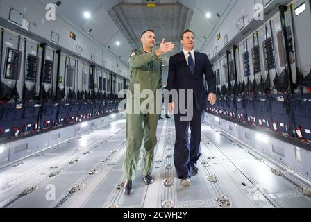 Britain's Prime Minister David Cameron views a newly delivered A400M Atlas aircraft with wing commander Simon Boyle at RAF Brize Norton, central England, November 27, 2014. The RAF will take delivery of 22 of the A400M aircraft. REUTERS/Peter Nicholls (BRITAIN - Tags: POLITICS MILITARY)