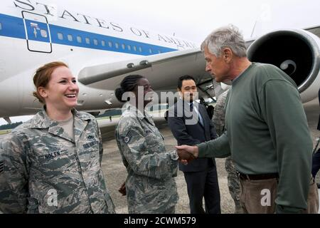 U.S. Air Force Staff Sgt. Sheri Nolen (L) and Staff Sgt. Denise Burris are greeted by U.S. Secretary of Defense Chuck Hagel (R) as he returns to the U.S. from Yokota Air Base October 4, 2013, ending his trip to South Korea and Japan. REUTERS/Jacquelyn Martin/Pool (JAPAN - Tags: MILITARY POLITICS) - Stock Photo