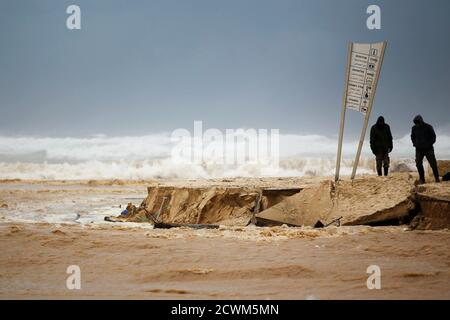 People look on the damage caused by a storm on a beach of the Mediterranean sea near Kibbutz Nitzanim December 13, 2013. A snowstorm of rare intensity blanketed the Jerusalem area and parts of the occupied West Bank on Friday, choking off the city and stranding hundreds in vehicles on impassable roads. REUTERS/Amir Cohen (ISRAEL - Tags: ENVIRONMENT)