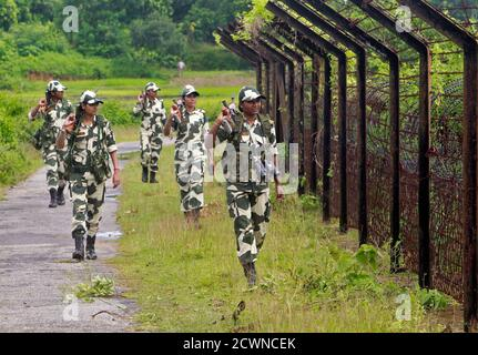 Female personnel of India's Border Security Force (BSF) patrol along the fencing of the India-Bangladesh international border ahead of India's Independence Day celebrations, at Dhanpur village in India's northeastern state of Tripura August 11, 2014. India commemorates its Independence Day on August 15. REUTERS/Jayanta Dey (INDIA - Tags: ANNIVERSARY MILITARY TPX IMAGES OF THE DAY) - Stock Photo