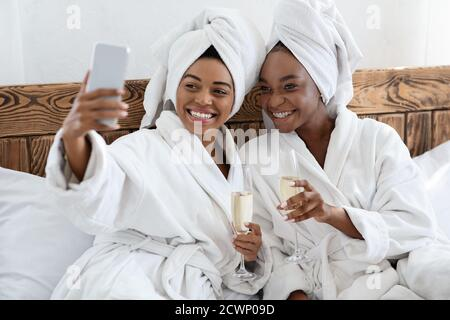 Stunning ladies in bathrobes sitting on bed and taking selfie