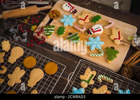 Freshly baked Christmas cookies on wooden table. Top view of xmas tree and snowman biscuits.