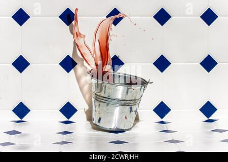 A metal bucket falls to the floor and splashes out the colored liquid.