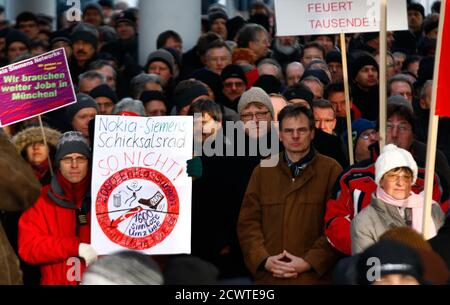 Employees of Nokia Siemens Networks (NSN) demonstrate in front of the German headquarters of NSN against job cuts in Munich February 1, 2012. Nokia Siemens Networks, the world's No.2 maker of mobile telecoms network equipment, plans to cut 4,100 jobs in its home countries of Finland and Germany as part of a cost-cutting drive aimed at coping with competition and weak demand.      REUTERS/Michael Dalder   (GERMANY - Tags: BUSINESS EMPLOYMENT TELECOMS) - Stock Photo