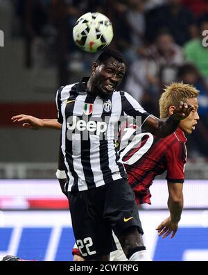 AC Milan's Keisuke Honda (R) challenges Juventus' Kwadwo Asamoah during their Italian Serie A soccer match at the San Siro stadium in Milan September 20, 2014.  REUTERS/Giorgio Perottino (ITALY - Tags: SPORT SOCCER) - Stock Photo
