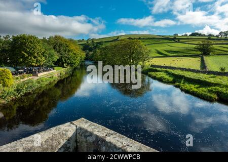 View up the River Wharfe from Burnsall bridge with green fields and blue sky, Yorkshire Dales National Park, UK